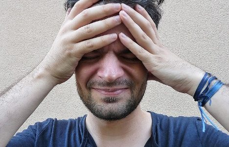 photo of man holding head with headache